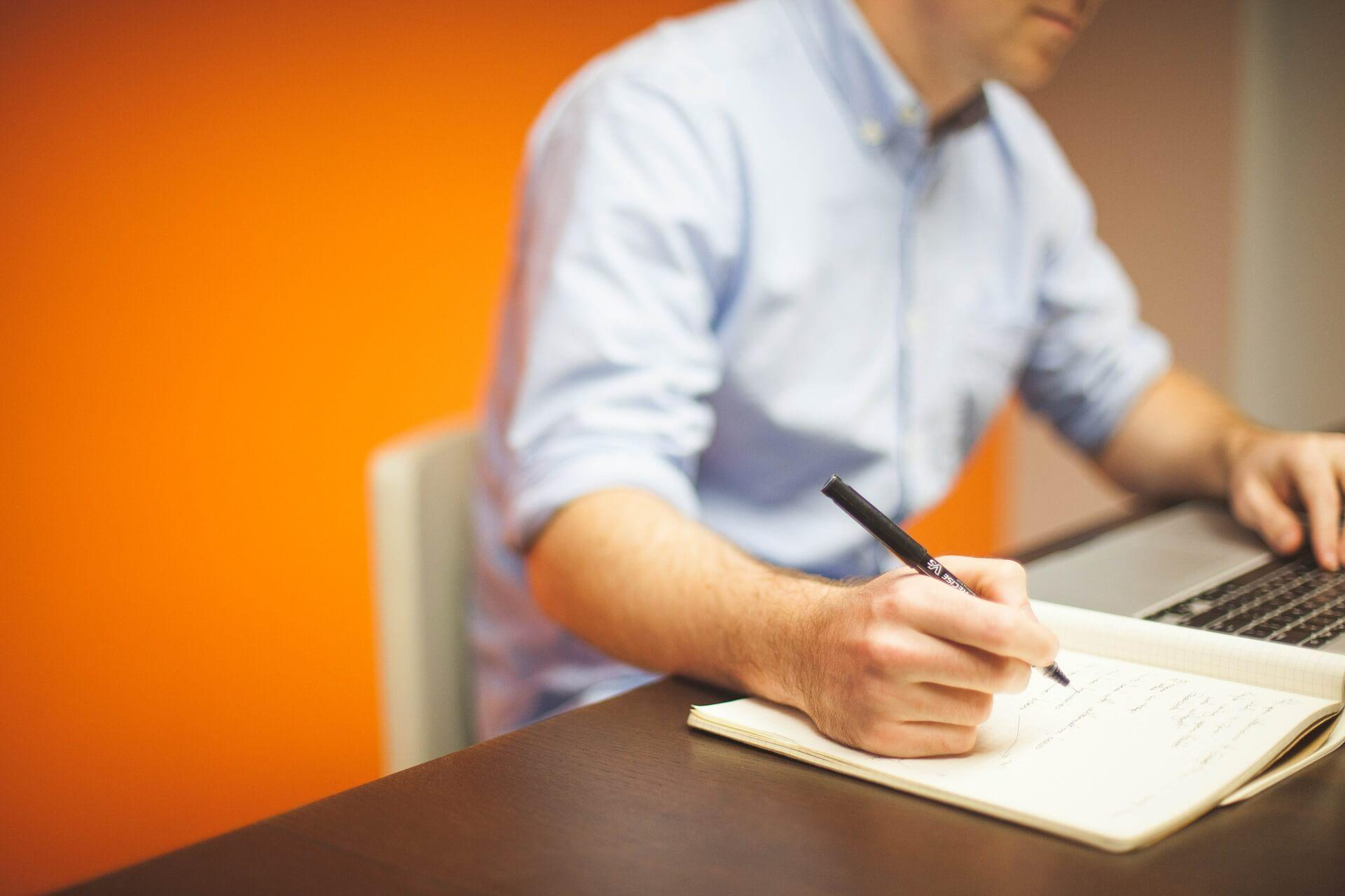 zdjęcie przedstawiające mężczyznę przed komputerem, który robi notatki