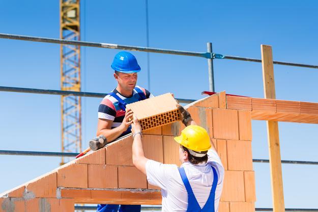 zdjęcie przedstawiające dwóch budowlańców podczas pracy